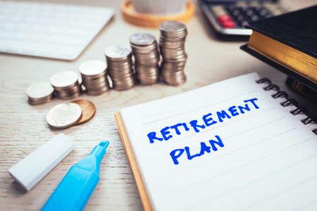 Zbliżenie tekstu planu emerytalnego pismem odręcznym na notebooku ze schodami sterty monet na biurku