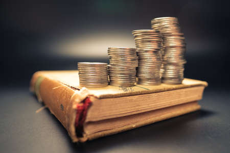 Saving heap coins stair on the old novel book, retirement planning, old financial information