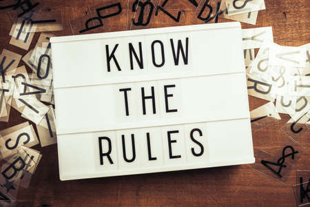 Know The Rules text on the lightbox with plastic alphabets scattered on wood background