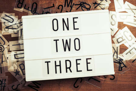 One, Two, Three step words on the lightbox with plastic alphabets scattered on wood background, three things procedure concept