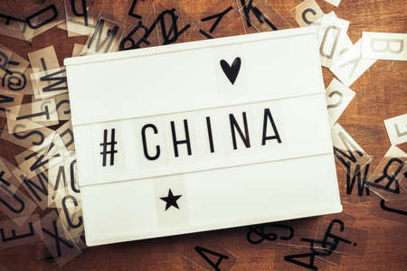China with hashtag on the lightbox with plastic alphabets scattered on wood background, China country related concept