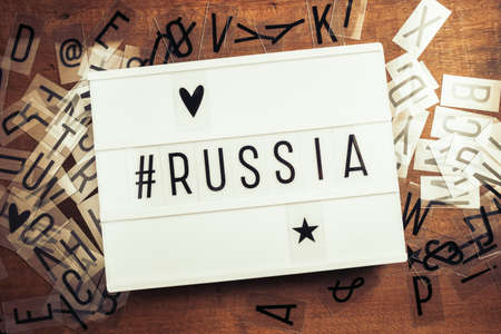 Russia with hashtag on the lightbox with plastic alphabets scattered on wood background, Russia country related concept