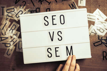SEO versus SEM, hand insert the letters on the advertising lightbox, concept for SEO and SEM or Search Engine Optimization and Search Engine Matketing