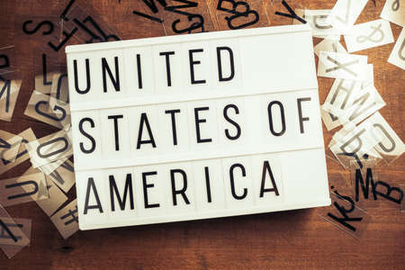 United States of America word on the lightbox with plastic alphabets scattered on wood background, USA country related concept