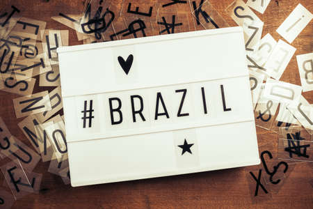 Brazil with hashtag on the lightbox with plastic alphabets scattered on wood background, Brazil country related concept