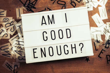 Am I Good Enough text on the lightbox with plastic alphabets scattered on wood background