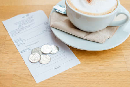 Coins change on the receipt and new cappuccino seved on the table Stok Fotoğraf