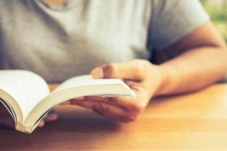 Zbliżenie kobieta w swobodnym materiale trzyma starą kieszonkową książkę do czytania