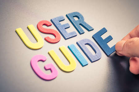 Hand place a wood alphabets as word USER GUIDE Stock Photo