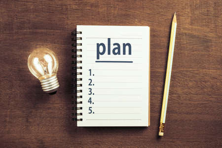 Plan lists on notepad with glowing light bulb, goal setting idea
