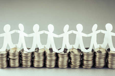 Paper human chain or teamwork symbol stand on the money heaps, team and budget, business startup or teamwork for success concept