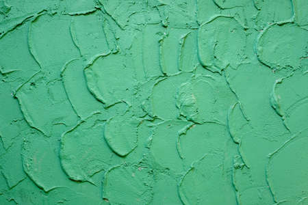 Concrete wall painted in green color with bulk coarse strokes texture