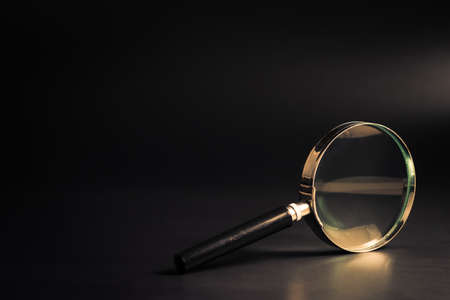 Magnifying glass on black background with space for text Stockfoto