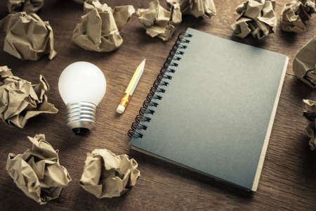Small light bulb glowing with opened notepad and crush paper balls, start writing and creative work concept