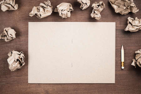 Opened recycle notepad as copy space with crush paper balls and short pencil