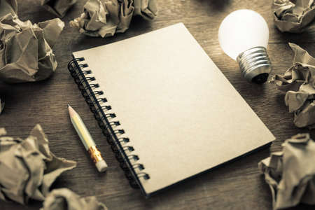 Recycle notepad with glowing light bulb and trash paper balls, creative writing concept Stockfoto