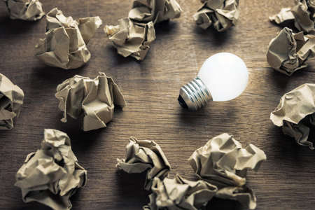 Light bulb glowing in the group of crumpled brown paper balls