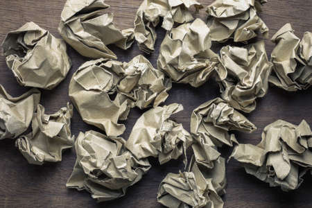 Many crumpled brown paper balls on wood table, create writing work concept