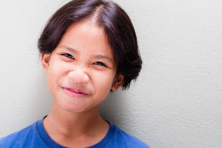 Closeup face of nine years old girl that try to stop laughing but still funny expression, pretty Thai girl