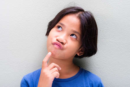 Nine years old Thai girl in blue t-shirt is looking up and thinking about something