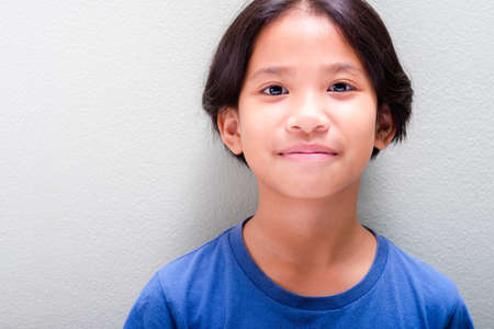 Headshot of nine years old Thai girl in blue t-shirt standing at the light green wall