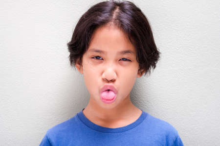 Nine years old Thai girl in blue t-shirt showing tongue