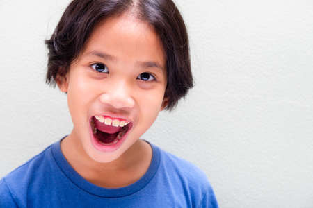 Nine years old Thai girl in blue t-shirt expresses feeling of surprise