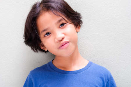 Headshot of nine years old Thai girl in blue t-shirt stand at the light green wall and smile Stockfoto