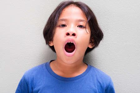 Une fille thaïlandaise de neuf ans en t-shirt bleu se fatigue et bâille
