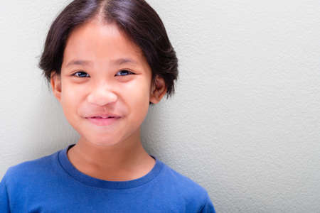 Nine years old Thai girl in blue t-shirt smiling on light green wall