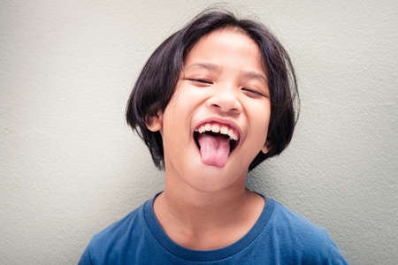 Child is fun laughing and show her tongue, nine years old Thai girl 免版税图像
