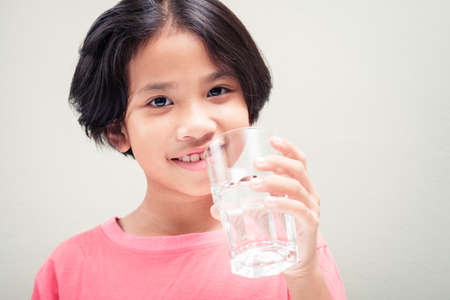 Nine years old girl smiling to camera and going to drink water from glass