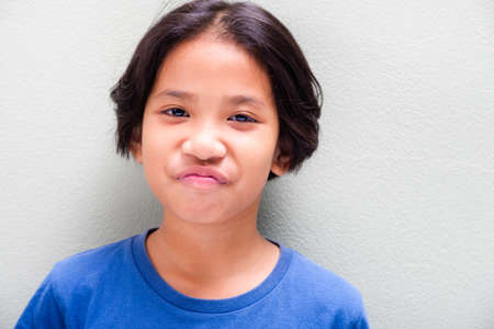 Nine years old Thai girl in blue t-shirt stand at the light green wall and expresses smile fade on her face