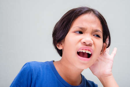 Nine years old girl is frustrated with hearing caused someone speak too quiet and cup her ear to hear better Stockfoto