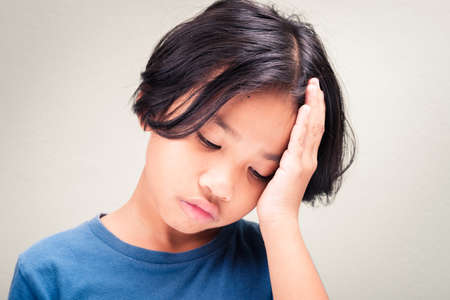 Nine years old girl touch her head and feel sick from headache