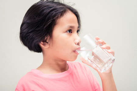 Nine years old girl in pink t-shirt drinking water from glass