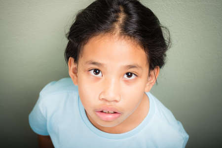 Nine years old Thai girl in casual t-shirt standing at the green wall and looking to camera
