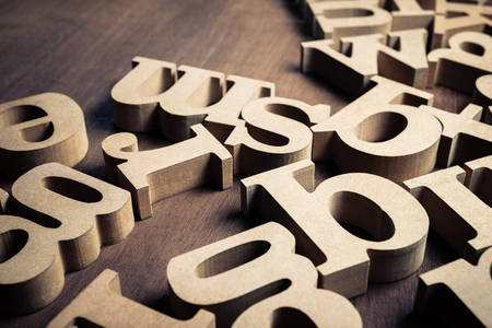 Closeup English thick wood alphabets on the table, abstract or background for English learning concept