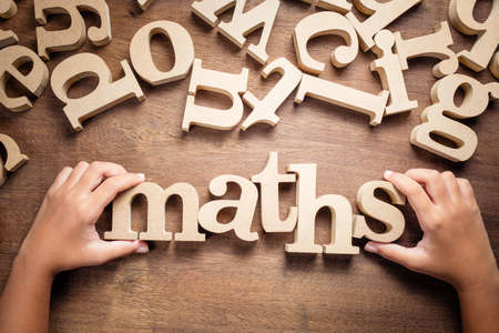 Closeup childs hand arrange wooden alphabets on the table as Maths word