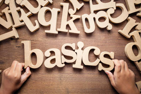 Closeup childs hand arrange wooden alphabets on the table as Basics word