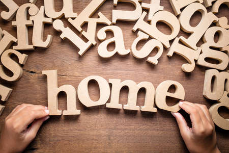Closeup childs hand arrange wooden alphabets on the table as Home word Stockfoto