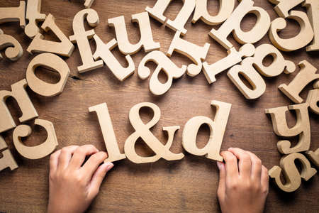 Closeup childs hand arrange wooden alphabets on the table as L&D abbreaviation, Learning and Development concept