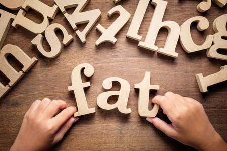 Closeup childs hand arrange wooden alphabets on the table as Fat word Stockfoto