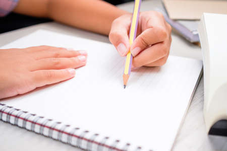 Closeup child going to write or draw something on notebook, child doing homework on the desk Stockfoto