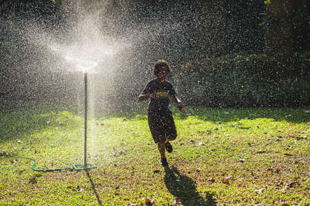 Nine years old girl is fun to run through the splash water of garden sprinkler