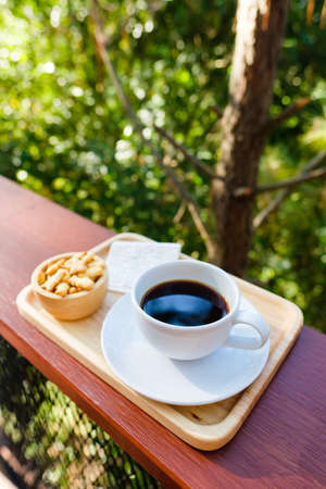 Black coffee in white cup and biscuits dessert on the balcony in the forest, afternoon coffee Stockfoto