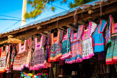 Colorful dress of Thai hill tribe style hanged for sale to the tourists at souvenir shop in local market, Northern of Thailand