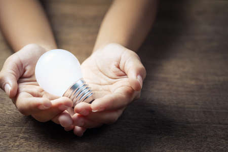 Closeup child hand hold the glowing small light bulb, got idea or energy concept Stockfoto