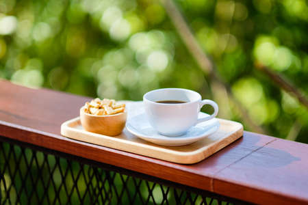 Black coffee in white cup and biscuits dessert on the balcony in the forest, afternoon coffee Stockfoto - 133548904