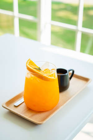 Orange juice with ice served on the white table in the restaurant
